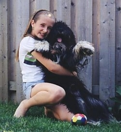 A blonde haired girl is hugging a black with white Polish Lowland Sheepdog. There is a wooden fence behind them.