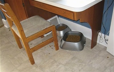 Two food Bowls under a kitchen table with a chair in front of them with scattered kibble on the floor