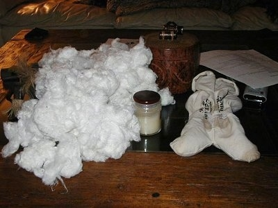 All of the Cotton from the Stuffed Animal, next to the outside of a stuffed animal on a coffee table