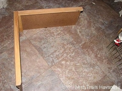 A wood divider that is used in a whelping box.