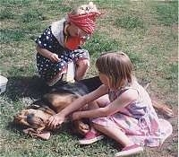 A girl in a blue polka dot dress and a red bandana is kneeling behind a sleeping Bloodhound. In front of it is a girl in a pink dress sitting in dirt.