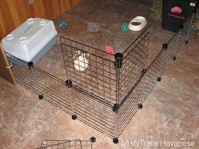 A wire rack enclosure that has a top rack being added to make it taller at the corner. There are dog toys, a food and water dish and a small carry type dog crate inside of the fenced off area.