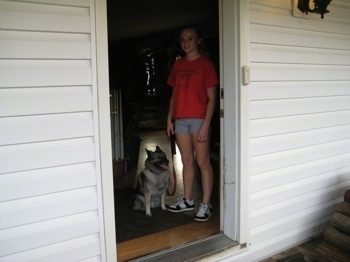 A blonde-haired girl is standing in a doorway next to a black, grey and white Norwegian Elkhound dog that is sitting.