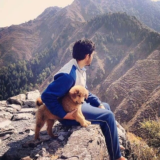 A man with dark black hair sitting outside at the edge of a cliff with a small tan puppy under his arm looking out at a good view of the mountains and valley.