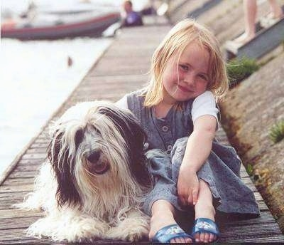 Front view - A grey and white with black Polish Lowland Sheepdog is laying on a wooden dock next to a girl sitting with blonde hair. They both are smiling. There is water next to them and a boat behind them.
