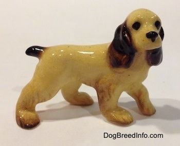 The left side of a tan with brown Cocker Spaniel figurine. The figurine has black circles for eyes and it has a short tail.