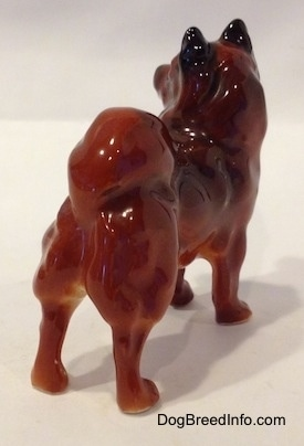 The back right side of a Chow Chow figurine that is in a standing pose. The figurine has its tail on its back.