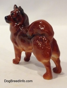 The back left side of a Chow Chow figurine that is in a standing pose. The figurine has a black muzzle.