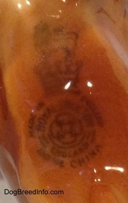 Close up - A Royal Doultan logo that is on the underside of a Chow Chow figurine.