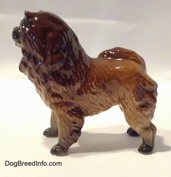 The left side of a brown with black Chow Chow figurine. The figurine has fine hair details. The figurine has black paws.