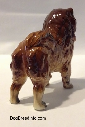 The back right side of a brown with black Chow Chow figurine.
