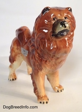 The front right side of a brown with tan and black Chow Chow figurine. The figurine has black eyes, inside ears and toe nails.