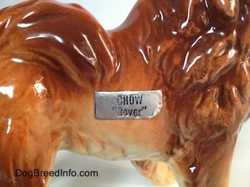 Close up - A sticker on a Chow Chow figurine. The sticker reads - Chow 'lover'.
