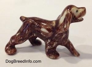 The right side of a Cocker Spaniel figurine painted with Aurasperse paint. The figurine has small black circles for eyes.