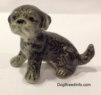 The left side of a black and gray Dandie Dinmont Terrier puppy in a sitting position figurine. The figurine has fine hair details and it has black circles for eyes. Its nose is black and its ears hang down to the sides of its head. Its snout is pushed back.