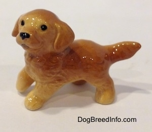 The left side of a Golden Retriever puppy figurine. The figurine has black circles for eyes and its ears are drapped along the side of its head.