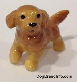 A figurine of a Golden Retriever puppy that is glossy and it has no paw details.