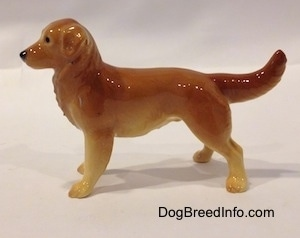 The left side of a brown with tan Golden Retriever. It is hard to differentiate the ears of the figurine from its body.