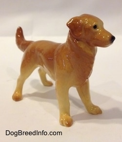 The front right side of a brown with tan Golden Retriever figurine. The figurine has long legs and small paws.