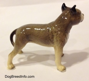 The right side of a black, gray and white figurine of a Pit Bull Terrier. The figurine has black ears.