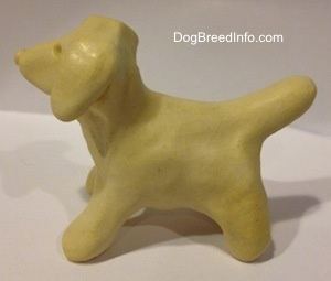 The left side of a ceramic white dog the has a medium sized tail and it is arched up.